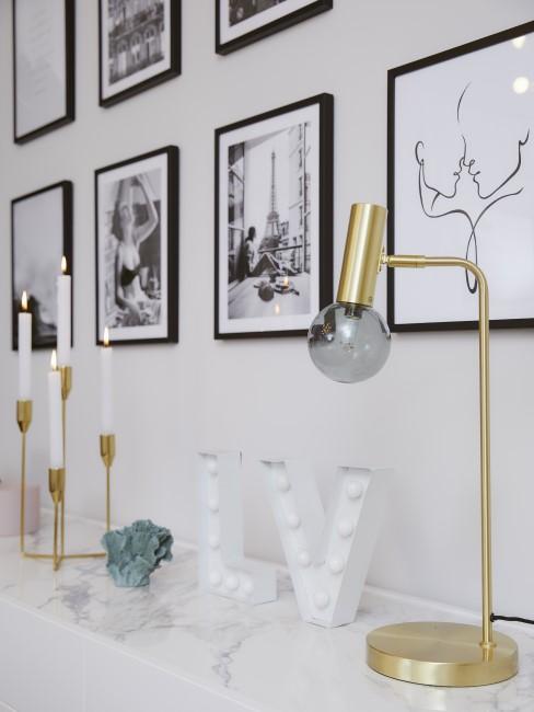 Entrada con cuadros y una lámpara de mesa dorada