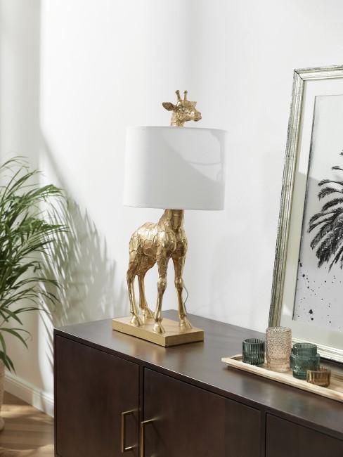 lámpara con forma e girafa en una comoda de madera