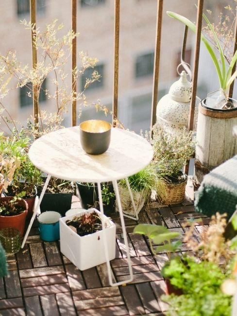 Balcon pequeño con mesa blanca y plantas