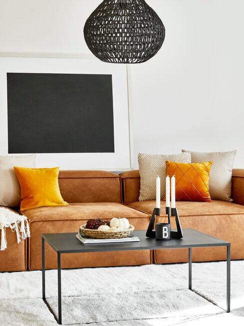 salón con sofá y cojines naranjas y deco negro