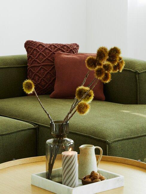 sofá verde con cojines terracota y flores