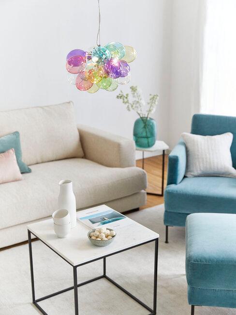 salón con sofá beige y sillón azul turquesa lámpara de colores
