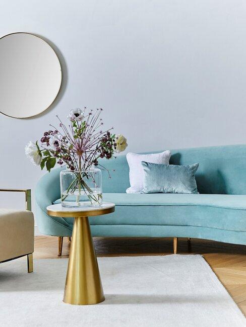 salón azul turquesa con mesa de metal dorada con flores