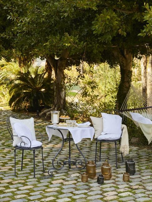 jardin con un suelo de piedra y una mesa de cafe con sillas de metal