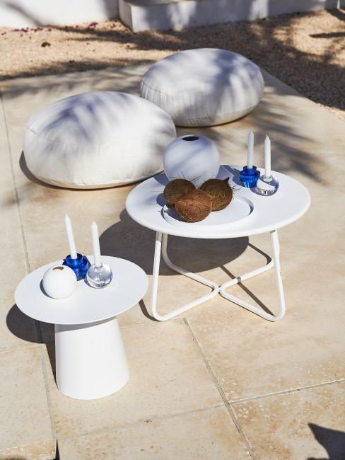 Terraz con mesas auxilares blancas y suelo de losa