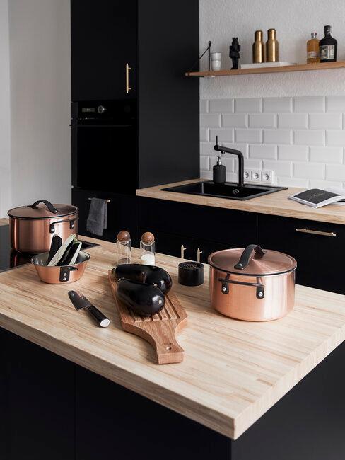 cocina negra con madera clara y accesorios color cobre