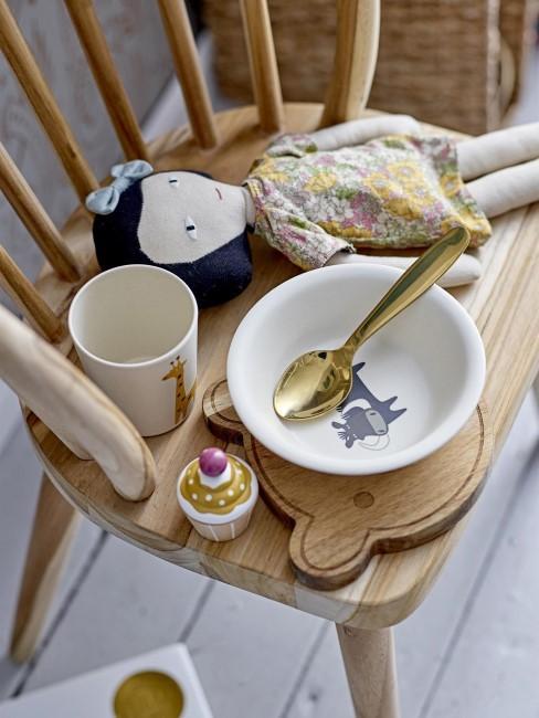 silla de madera con una vajilla y un juguete infantil