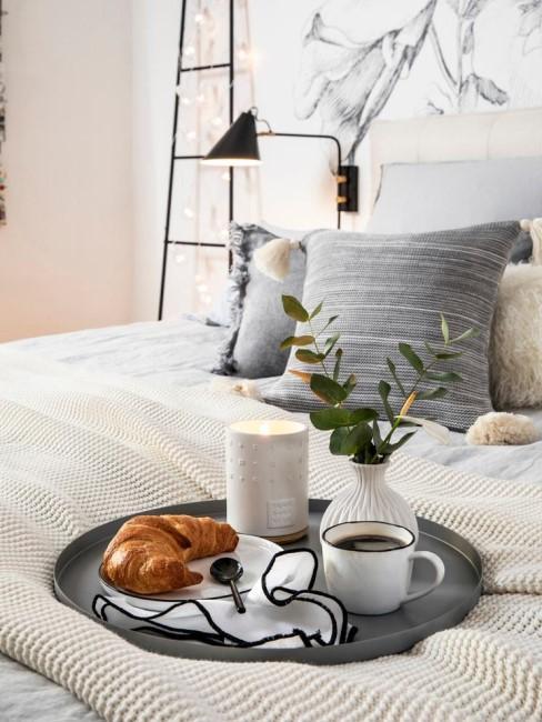 Café con desayuno en un bandeja en la cama