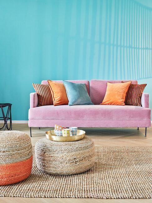 sofá rosa con cojines de colores y pufs de ratán