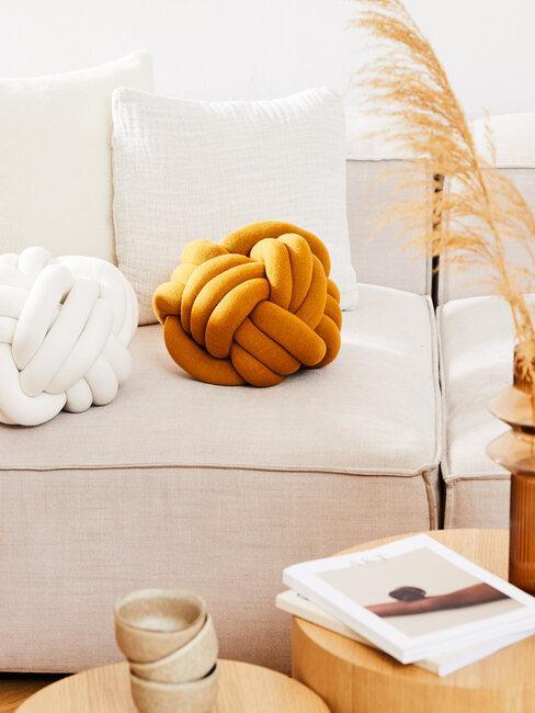 cojin naranja con sofá y cojines blancos