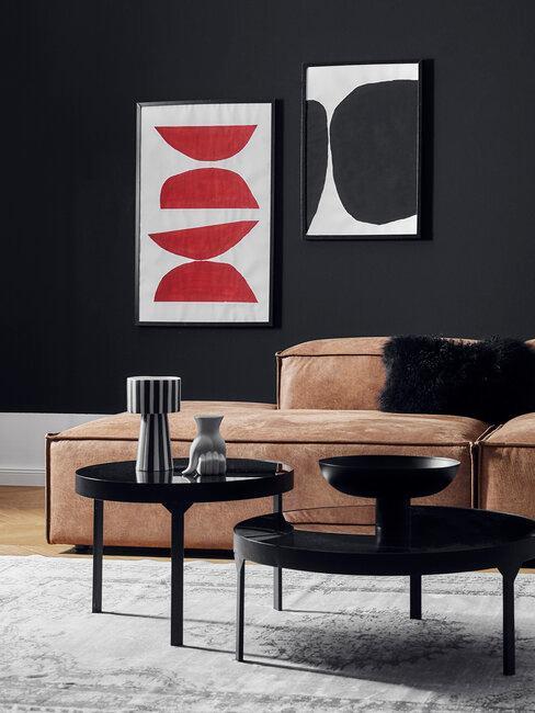 salón con pared y mesas negras sofá de cuero marrón y cuadros pared