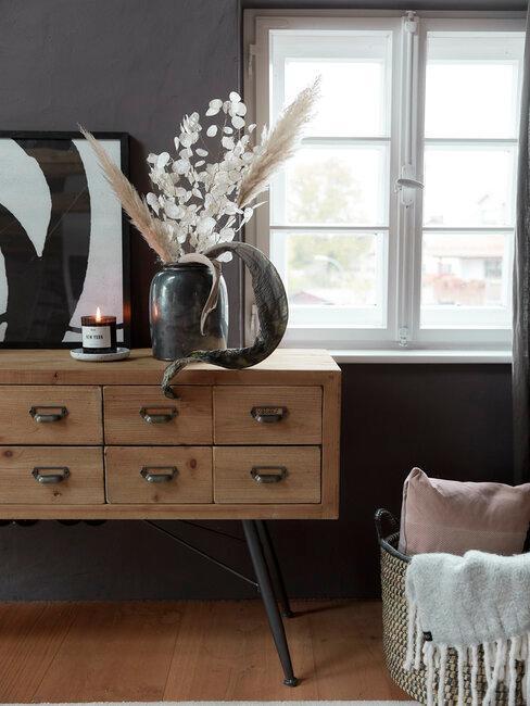 mueble de madera con cajones jarrón con flores y pared gris