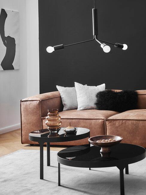 salón con pared mesas y lámpara negras sofá marrón de cuero