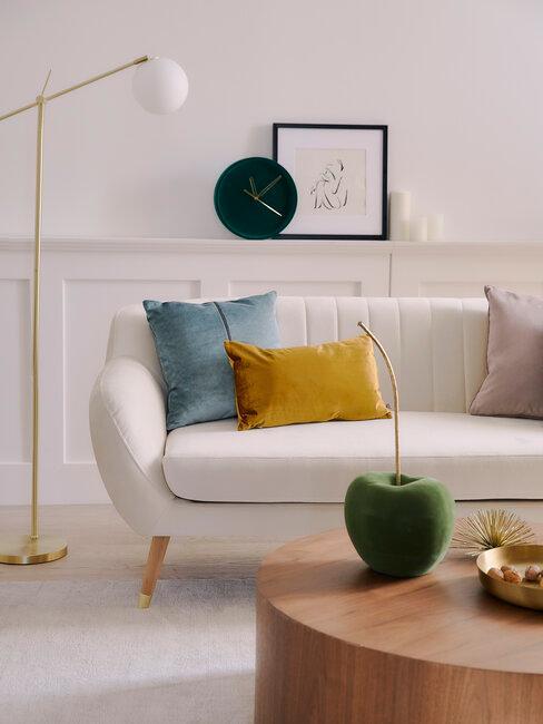 salóncon sofá blanco cojines de colores mesa de madera y cuadros