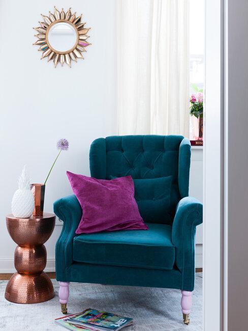 mesa de bronce sillón azul y cojin morado