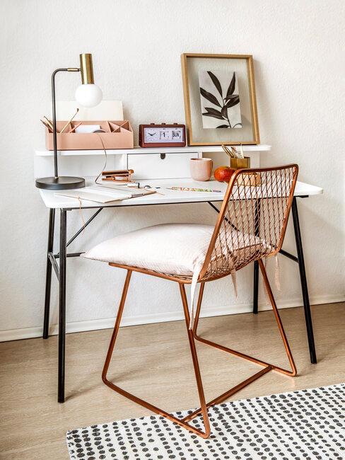 silla metálica de bronce con escritorio blanco