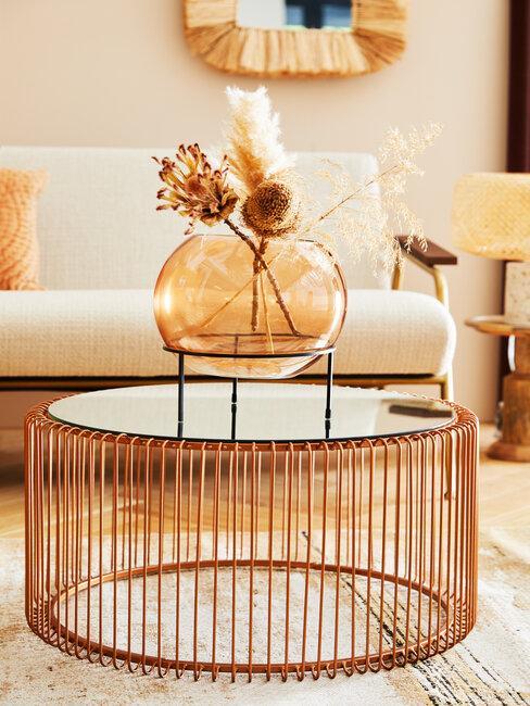 mesa de metal bronce y jarrón de cidrio con flores secas