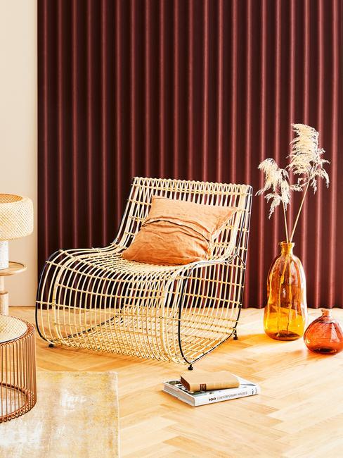 sillón de mimbre con cojín y jarrones de cristal naranja