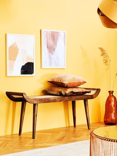 pared amarilla con cuadros y banco de madera