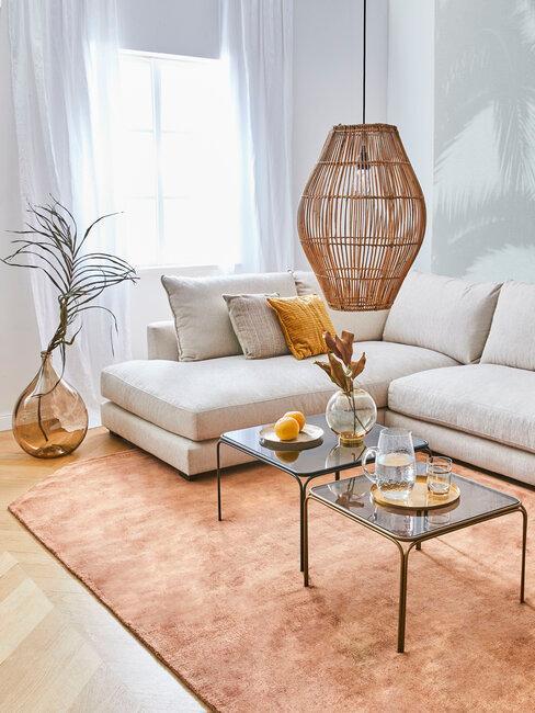 salón con sofá beige alfombra naranja jarrón cristal y lámpara boho