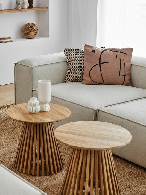 sofá beige con cojines t mesas de maderea con jarrones
