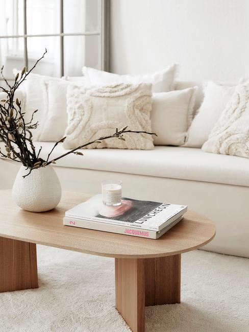 sofá y jarrón blanco y mesa de madera