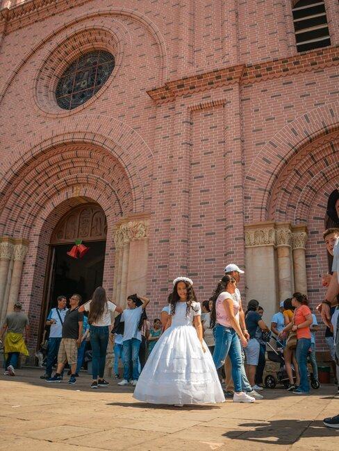 niña con vestido de comunión frente iglesia