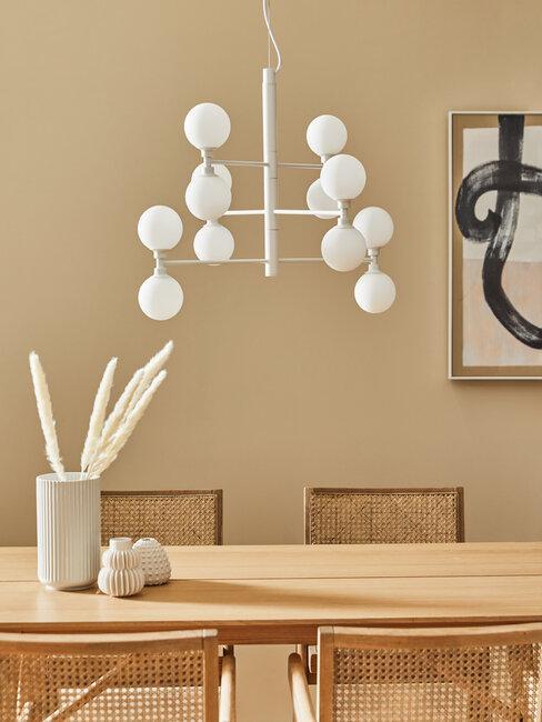 mesa y sillas de madera, pared beige, lámpara y accesorios blancos