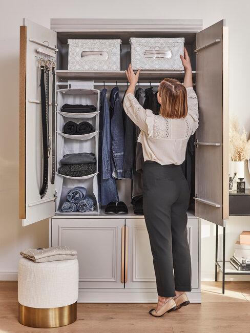 mujer guarda en armario ropa ordenada