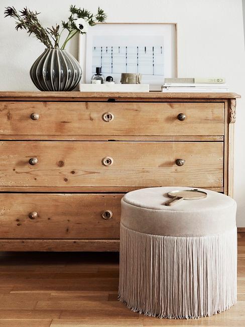 cómoda de madera y puf de flecos