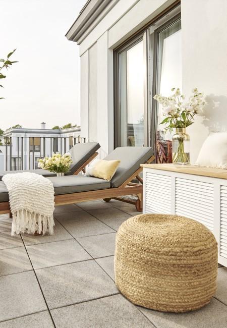 Puf de mimbre en una terraza con hamacas