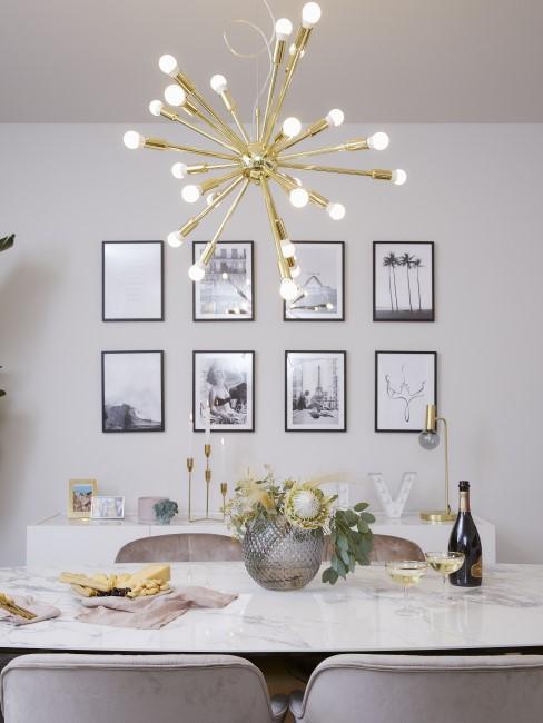 Pared en gris decorada con cuadros en blanco y negros y una lampara dorada