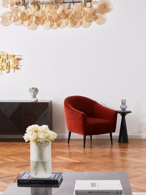 salón con sillón rojo lámpara y flores