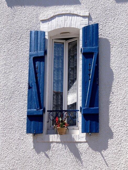 ventanas azules con flores en casa de cal