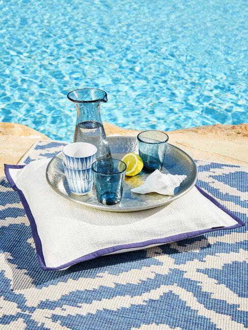 piscina, cojin y bandeja con vasos azules