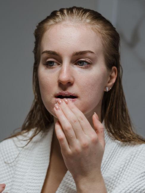 mujer aplicando exfoliante labios