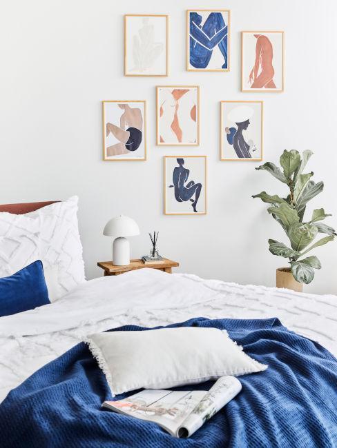 dormitorio azul y blanco con cuadros y planta