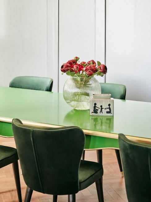 mesa y sillas verdes con jarrón con flores