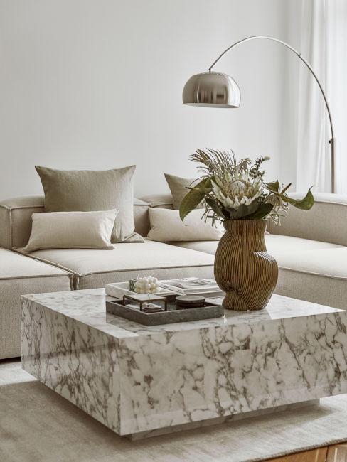 sofá, mesa de mármol, jarrón con flores secas y lámpara metal