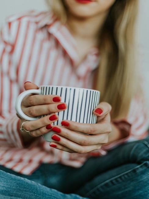 taza de rayas y manos con uñas rojas
