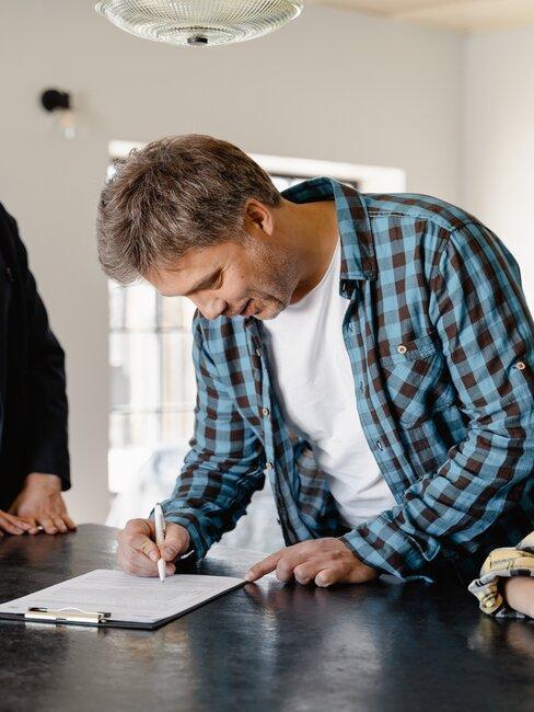hombre firmando documento