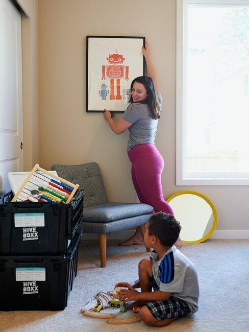 mujer colgando cuadro con niño