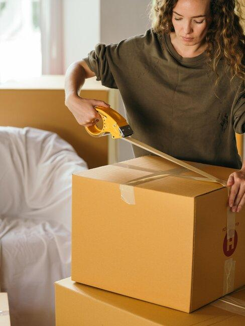 mujer cierra caja mudanza