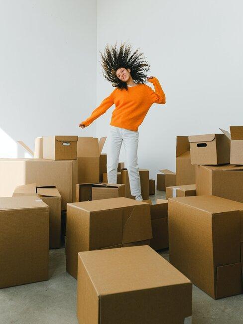 mujer bailando entre cajas de mudanza