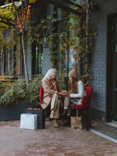 Mujer joven y mayor sentadas exterior