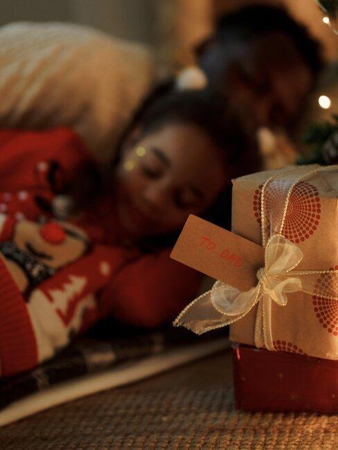 niña durmiendo frente a caja de regalos