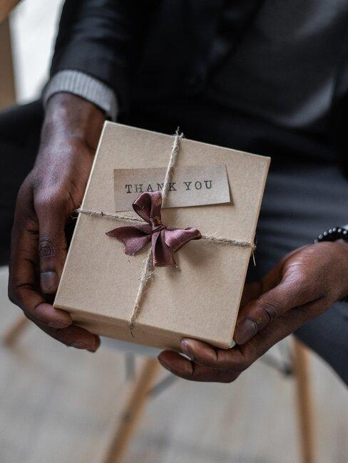 hombre sostiene caja de regalo