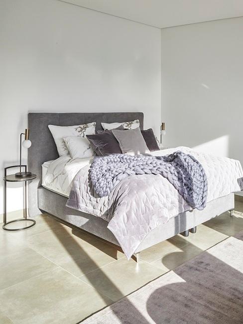 cama gris con mantas