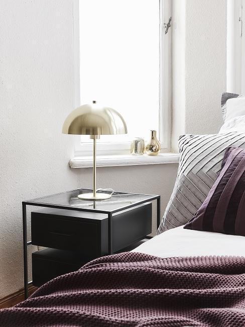 mesa de noche negra en dormitorio blanco
