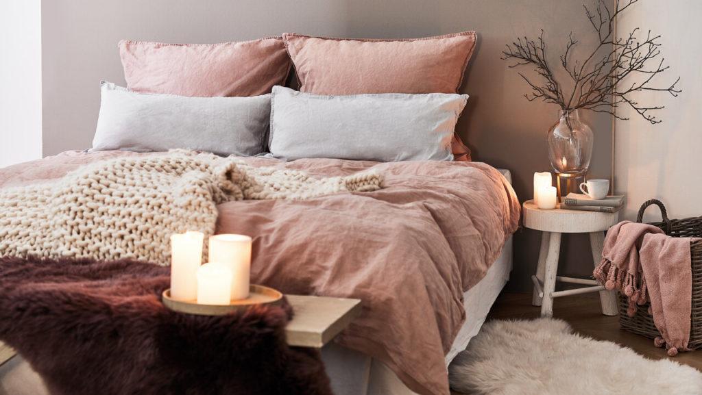 dormitorio rústico con decoración salmón, velas y ramas
